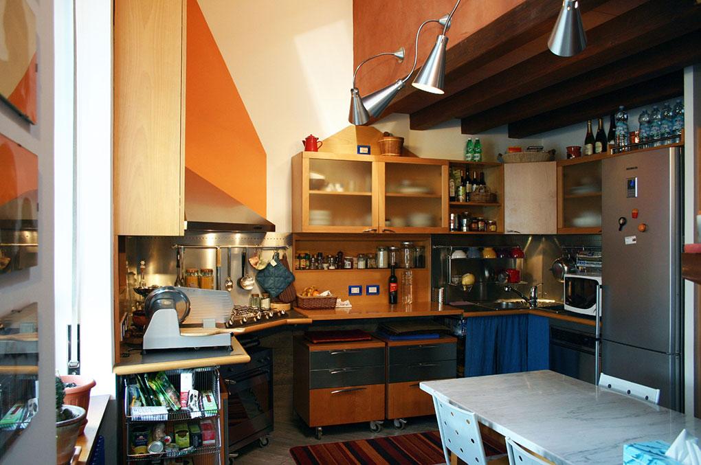 Abitare su due livelli - Vista cucina e cappa angolare in acciaio