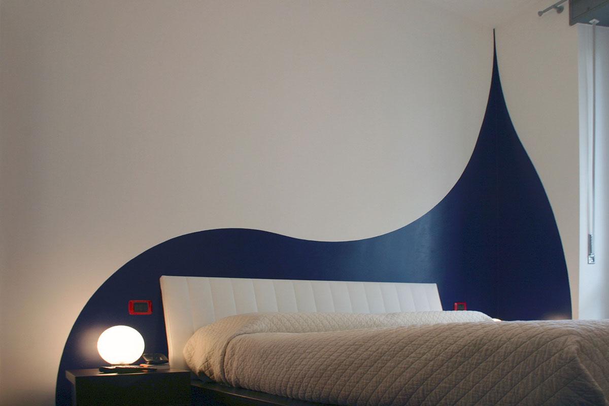 Colore arredo - Una colata di colore che incornicia la testata del letto