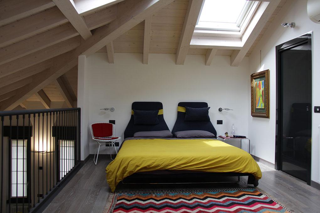 Il sottotetto diventa loft - Camera da letto con tetto in legno sbiancato a vista
