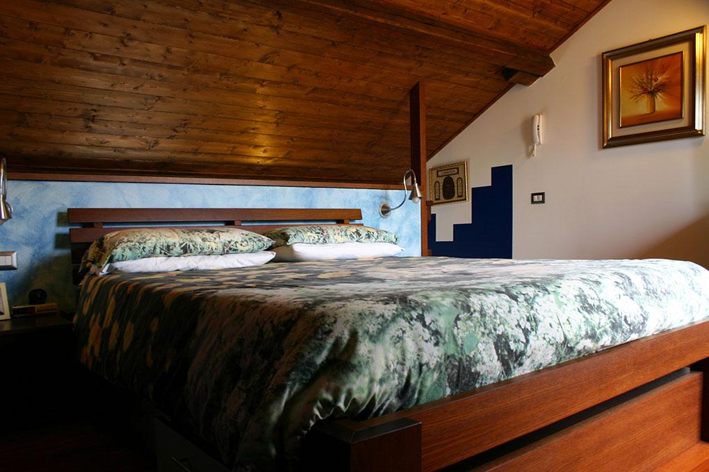 Recupero di sottotetto - Camera da letto con travi in legno a vista